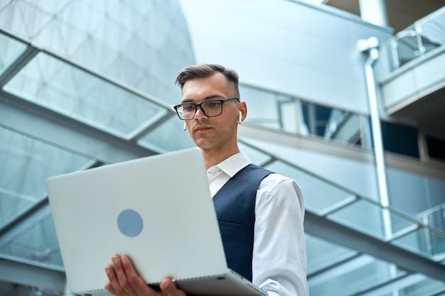 Jonge man met een laptop in een zakencentrum.