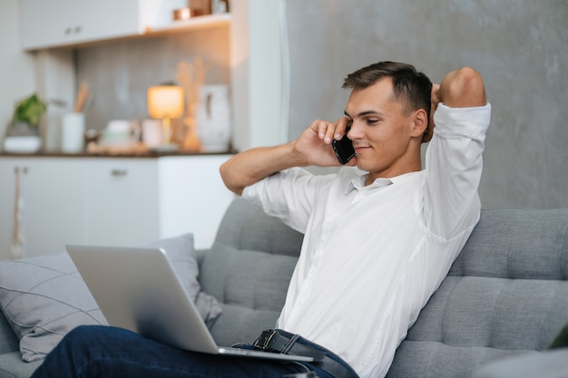 Jonge man met een laptop praten op een smartphone.