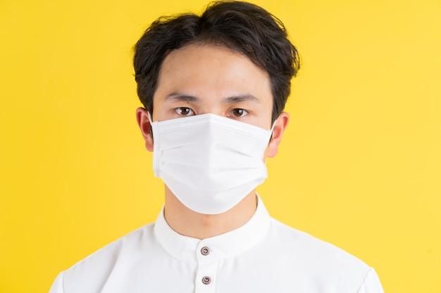 Jonge man met een masker staan en kijken naar de voorkant op geel