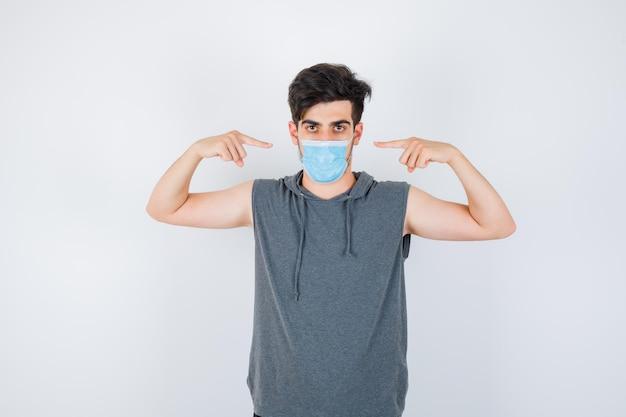Jonge man met een masker terwijl hij zichzelf in een grijs t-shirt wijst en er serieus uitziet