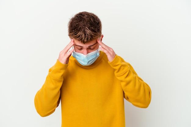 Jonge man met een masker voor coronavirus geïsoleerd op een witte achtergrond tempels aan te raken en hoofdpijn te hebben.