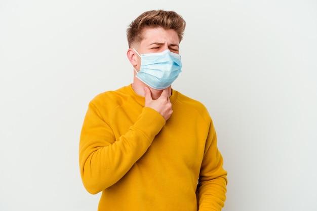 Jonge man met een masker voor coronavirus geïsoleerd op een witte muur lijdt aan keelpijn als gevolg van een virus of infectie