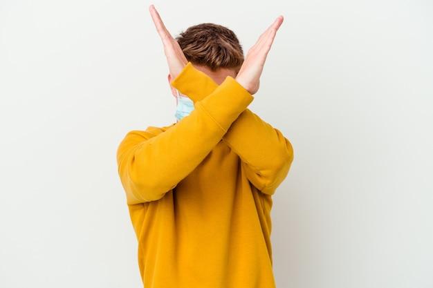 Jonge man met een masker voor coronavirus geïsoleerd op een witte muur met twee armen gekruist