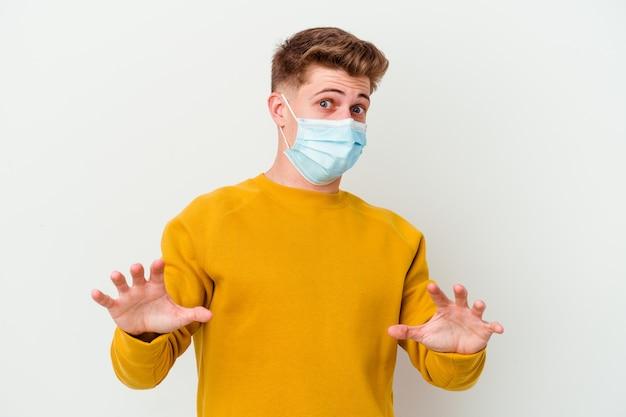 Jonge man met een masker voor coronavirus geïsoleerd op een witte muur wordt geschokt vanwege een dreigend gevaar