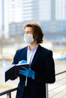 Jonge man met een medisch masker buiten, geen geld, crisis, armoede, ontbering. corona-isolatie.