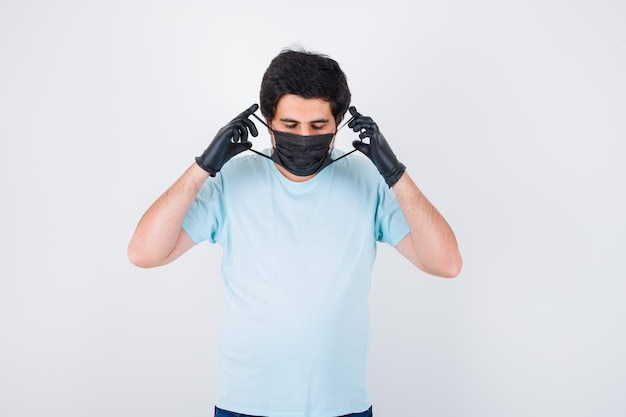 Jonge man met een medisch masker in shirt, spijkerbroek en ziet er verstandig uit. .