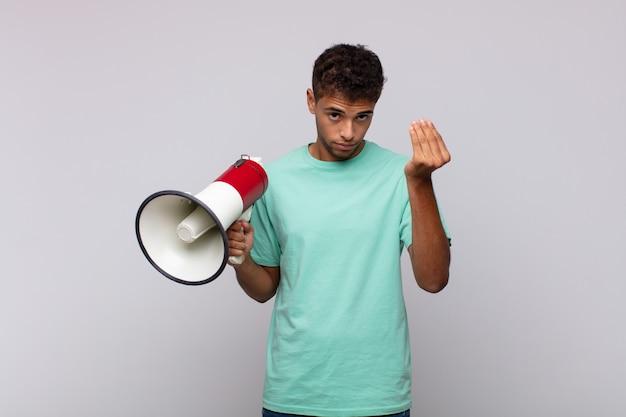 Jonge man met een megafoon die capice of geldgebaar maakt en je vertelt je schulden te betalen!