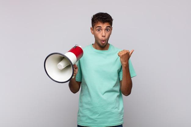Jonge man met een megafoon die verbaasd kijkt in ongeloof, wijzend naar een object aan de zijkant en zeggen wow, ongelooflijk
