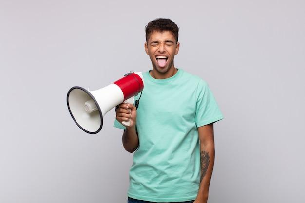 Jonge man met een megafoon met vrolijke, zorgeloze, rebelse houding, grappen maken en tong uitsteken, plezier maken
