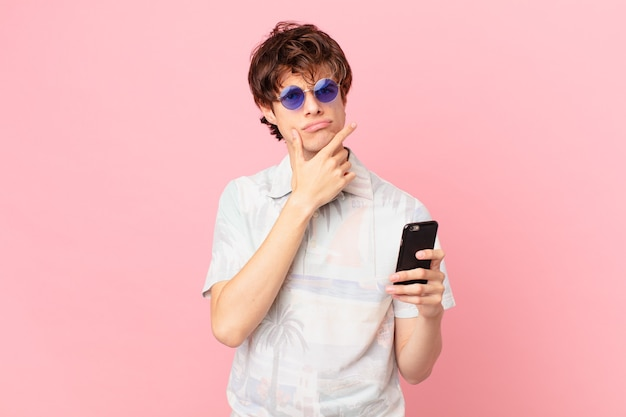 Jonge man met een mobiele telefoon denken twijfelachtig en verward te voelen