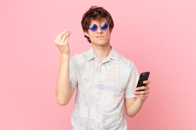 Jonge man met een mobiele telefoon die capice of geldgebaar maakt en zegt dat je moet betalen