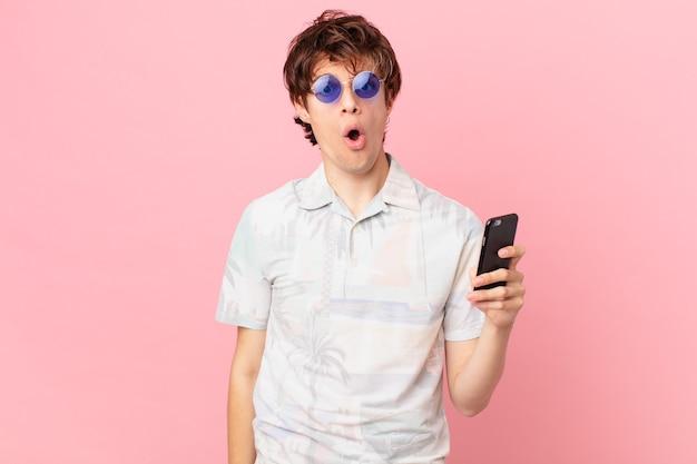 Jonge man met een mobiele telefoon die erg geschokt of verrast kijkt