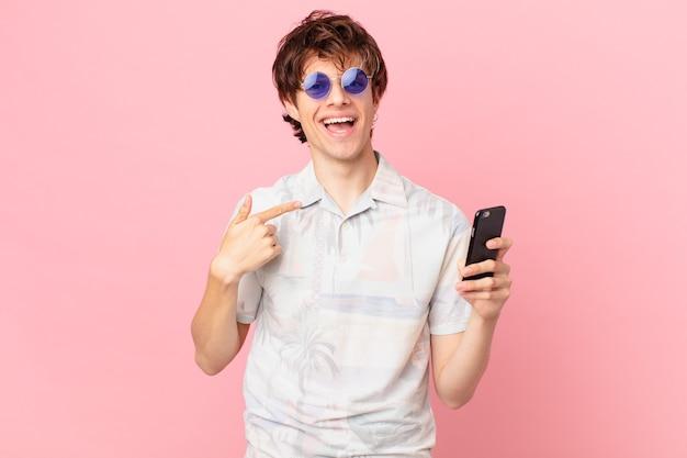 Jonge man met een mobiele telefoon die zich gelukkig voelt en naar zichzelf wijst met opgewonden