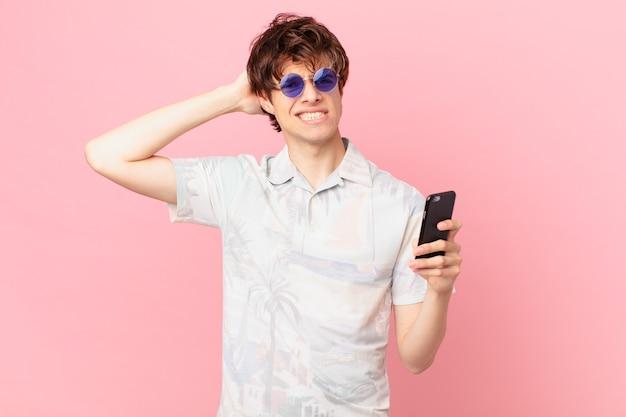 Jonge man met een mobiele telefoon die zich gestrest, angstig of bang voelt met de handen op het hoofd