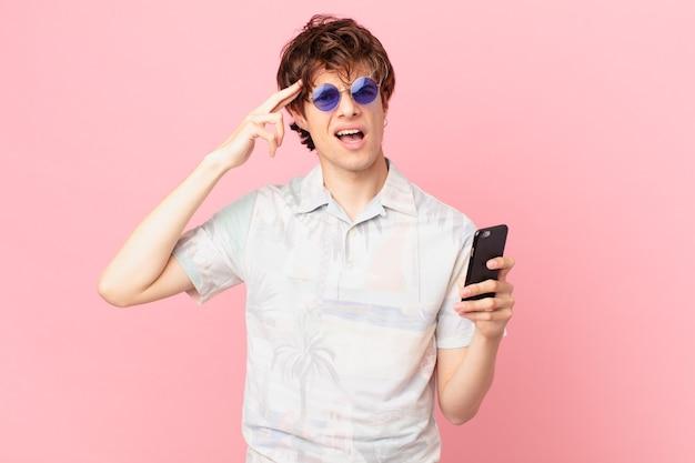 Jonge man met een mobiele telefoon die zich verward en verbaasd voelt en laat zien dat je gek bent