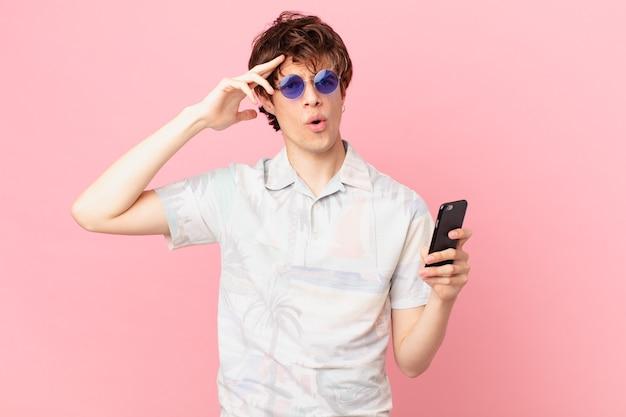 Jonge man met een mobiele telefoon kijkt blij verbaasd en verrast