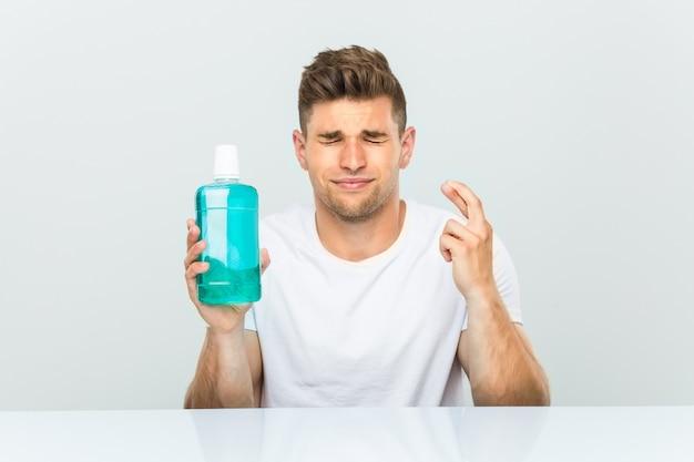 Jonge man met een mondwater kruising vingers voor het hebben van geluk