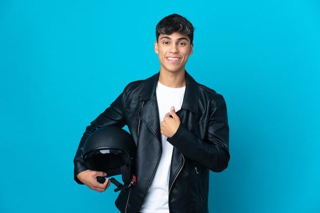 Jonge man met een motorhelm over geïsoleerde blauwe muur met verrassingsgelaatsuitdrukking