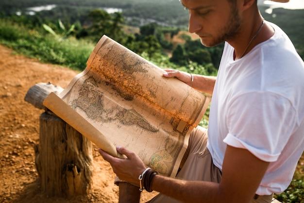 Jonge man met een papieren kaart buitenshuis