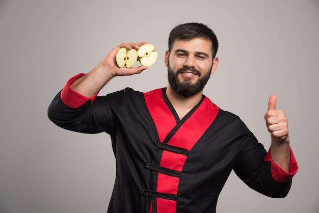 Jonge man met een plakje verse appel.