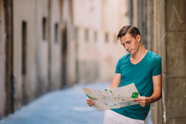 Jonge man met een plattegrond van de stad in europese stad.