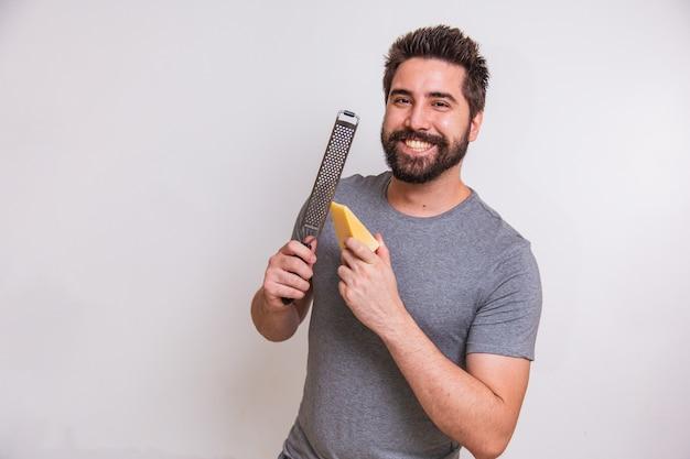 Jonge man met een rasp en een stukje kaas in zijn hand op een grijze achtergrond. man zal de kaas raspen