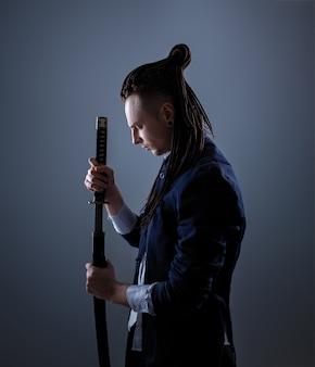 Jonge man met een samurai zwaard. glamourfoto.