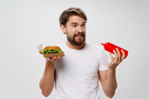 Jonge man met een sappige hamburger in zijn handen, een man die een hamburger eet