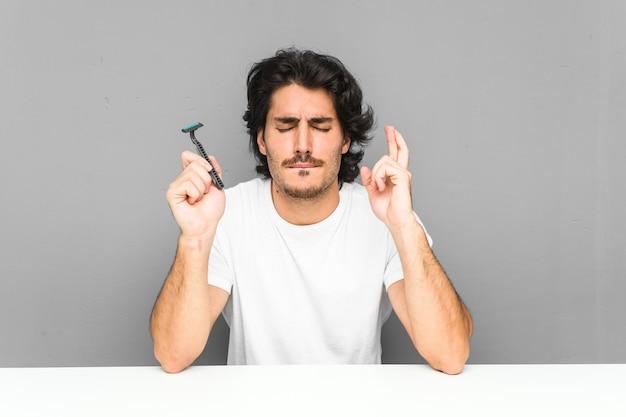 Jonge man met een scheermesje dat zijn vingers kruist om geluk te hebben