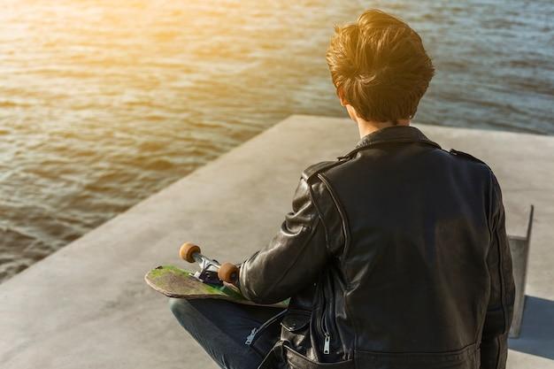 Jonge man met een skateboard in de buurt van de zee