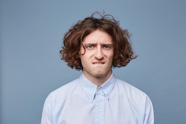 Jonge man met een slordig kapsel wordt op zijn lip gedrukt