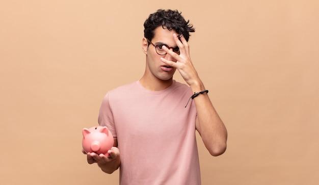 Jonge man met een spaarvarken die geschokt, bang of doodsbang kijkt, gezicht bedekt met hand en tussen vingers gluurt