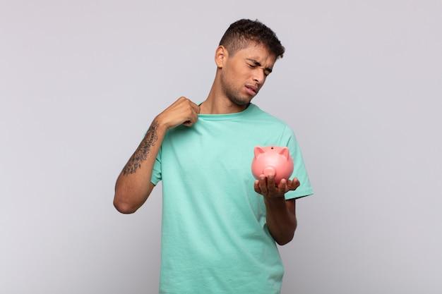 Jonge man met een spaarvarken die zich gestrest, angstig, moe en gefrustreerd voelt, de nek van het shirt trekt, gefrustreerd kijkt door het probleem