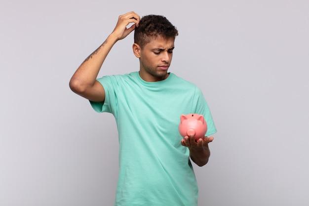 Jonge man met een spaarvarken die zich in verwarring en verwardheid voelt, zijn hoofd krabt en naar de zijkant kijkt