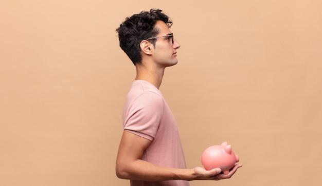Jonge man met een spaarvarken op profielweergave die ruimte vooruit wil kopiëren, denken, zich voorstellen of dagdromen