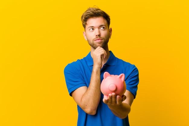 Jonge man met een spaarvarken tegen oranje achtergrond