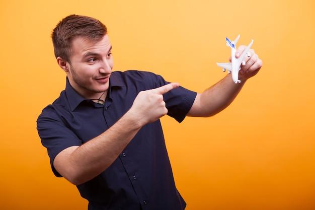 Jonge man met een speelgoedvliegtuig in blauw shirt over gele achtergrond. avonturen moeten nog komen