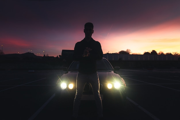 Jonge man met een sportwagen op een parkeerplaats met gekleurde lichten Premium Foto
