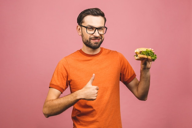 Jonge man met een stuk hamburger. student eet fastfood. erg hongerige man. duimen omhoog.