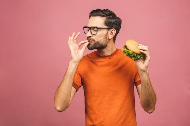 Jonge man met een stuk hamburger. student eet fastfood. hamburger is niet behulpzaam. erg hongerige man. dieet concept.