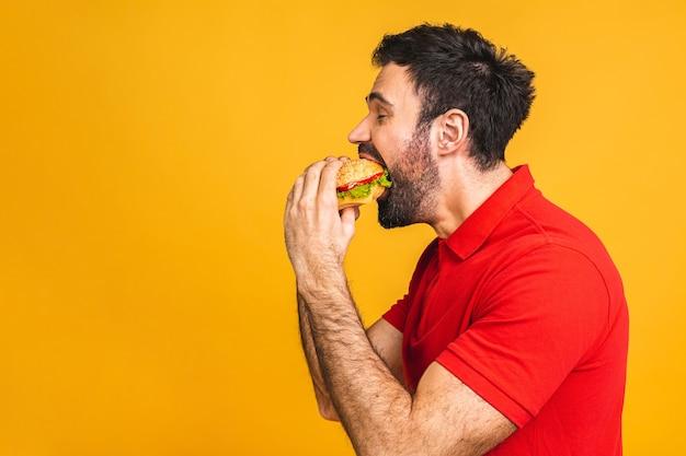 Jonge man met een stukje sandwich. student eet fastfood. hamburger is geen nuttig voedsel.