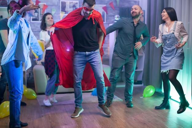 Jonge man met een superheldenkostuum in een kamer met ballonnen die dansen met zijn vrienden.