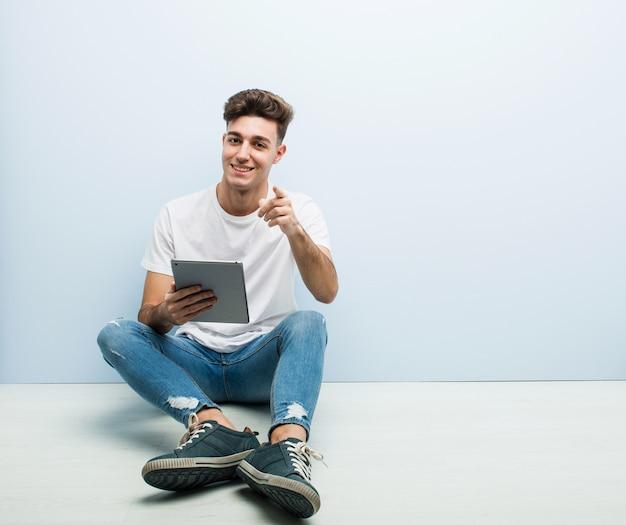 Jonge man met een tablet zit indoor vrolijke glimlach wijst naar voren.