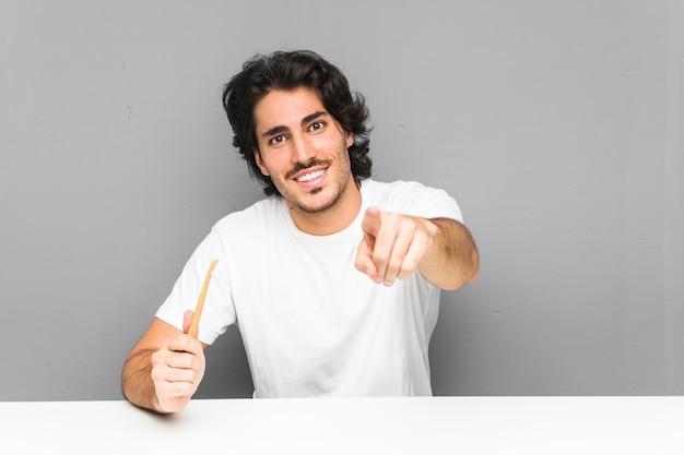 Jonge man met een tandenborstel vrolijke glimlach wijzend naar de voorkant