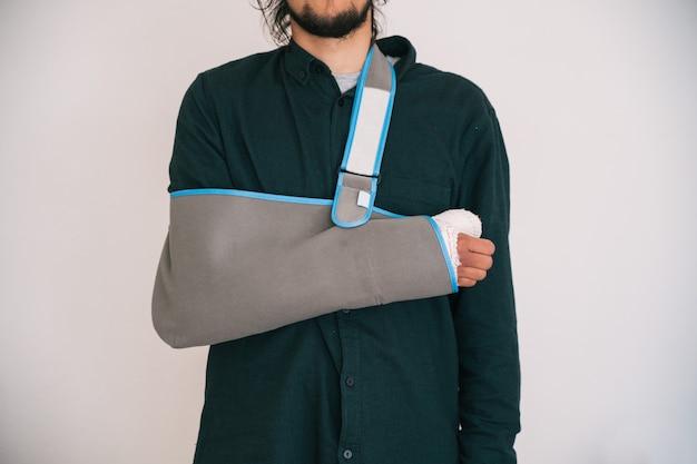 Jonge man met een verbonden arm en een textielen slinger die zijn arm vasthoudt