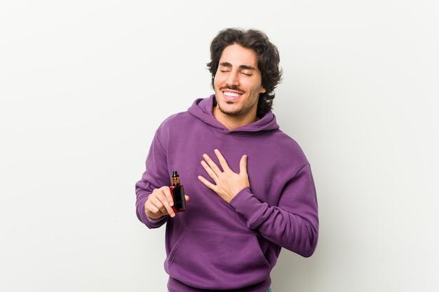 Jonge man met een verdamper lacht hardop terwijl hij de hand op de borst houdt