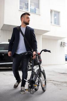 Jonge man met een vouwfiets in de stad