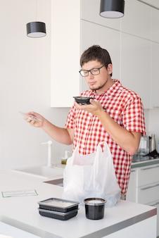 Jonge man met een wegwerp plastic zak met voedselbezorging in de moderne keuken, ruikend eten uit de doos
