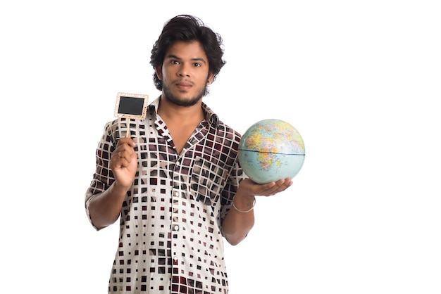 Jonge man met een wereldbol en een klein bord op een wit.