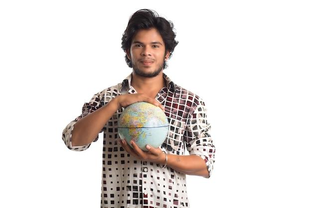 Jonge man met een wereldbol op een wit.